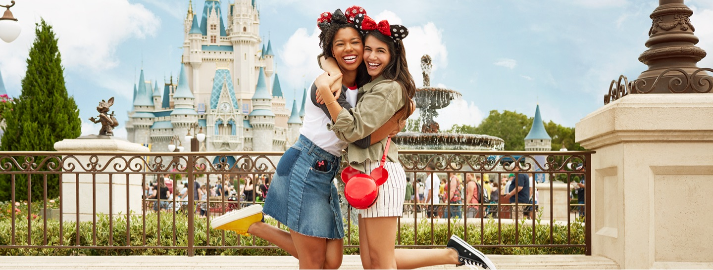 Two girls hugging in front of a Disney Castle